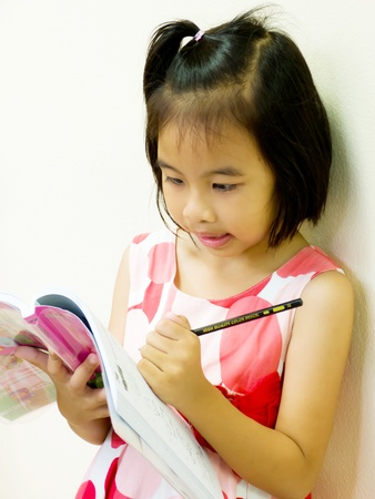 Young Girl writing and reading her homework photo