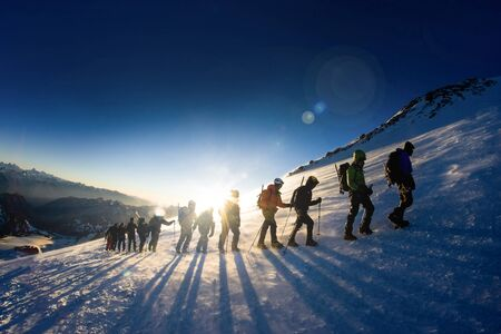 A group of tourists with backpacks and crampon walking one after another goes to the top of the mountain on a snowy ice slope