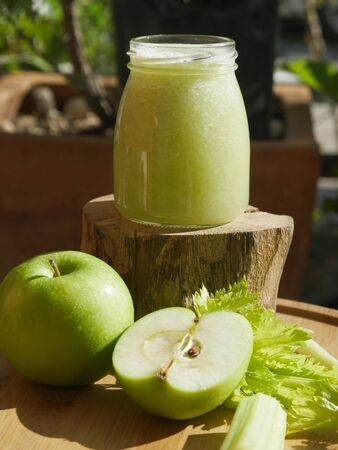 glass bottle for green smoothie detox with apple and parsley on the wood and horizontal view from above