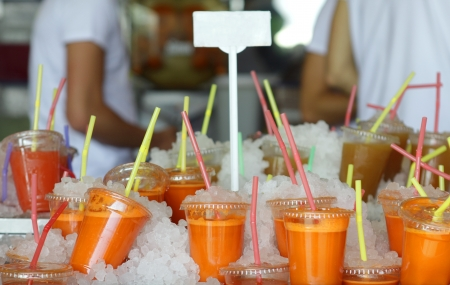 Plastic glasses with cold freshly squeezed carrot juice at Tel-Aviv market