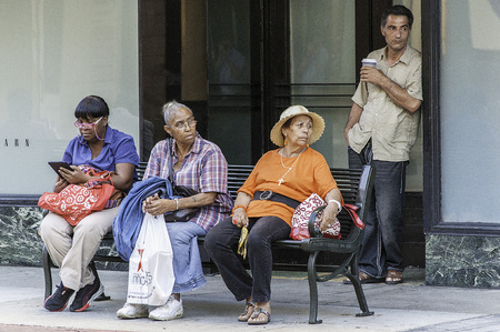 group of people sitting on bus bench, interesting expressions.