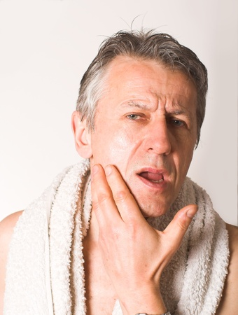 mirror on the water: Matured, white man with a towel around his neck, uses his favourite after shave against mirror in his bathroom