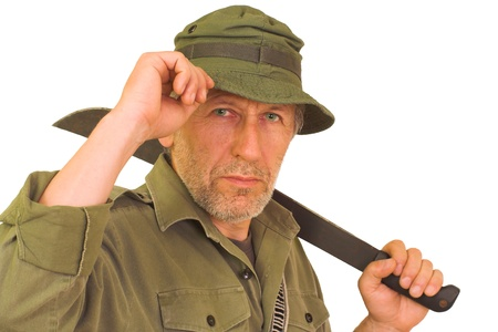 explorer: Horizontal portrait of a beardy man with a wrinkled face, wearing a green hut and a shirt  He keeps a bush knife on his back