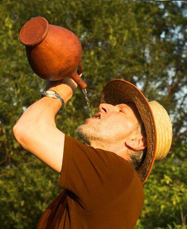 llegar tarde: Vertical de la imagen hecha en sofocante tarde a un hombre de agua potable de una jarra. Es beardy, parece estar sediento y cansado, y lleva una choza de paja. Foto de archivo