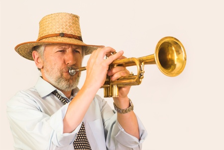 graying: Horizontal image showing a matured, graying, unshaved trumpeter over 50 wearing a straw hut. His face is wrinkled, but happy, his eyes closed. He plays a brass trumpet. An effort visible on his face.