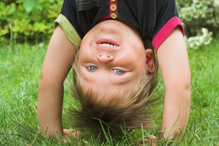 kinder garden: Little boy plays on the playground, standing upside down, his hands in the grass