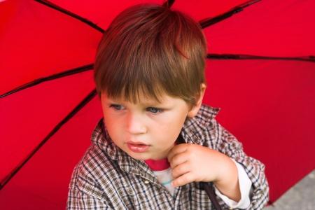 jardin de infantes: Ni�o peque�o con un paraguas rojo en su mano est� escuchando la lluvia Su rostro recogido