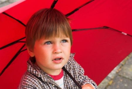 kinder garden: Little boy with a red umbrella in his hand is listening to the rain  His face collected  Stock Photo
