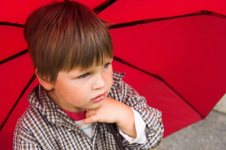 Little boy with a red umbrella in his hand is listening to the rain  His face collected Stock Photo - 14484039