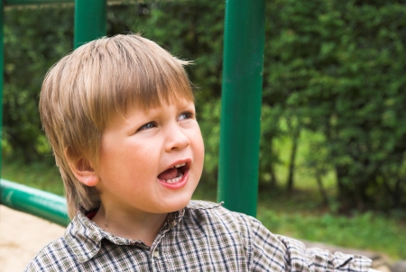 kinder garden: Little boy plays on the playground, shouting and singing