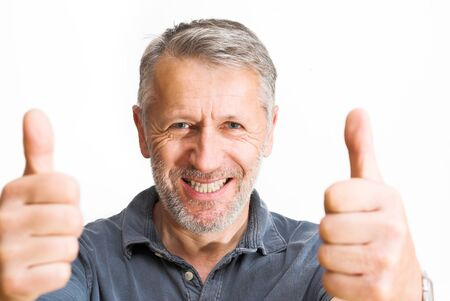 optimist: The optimist  Graying man rises both thumbs with a wide, bright smile Stock Photo