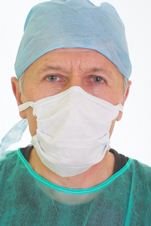 urologist: A portrait of surgeon tired face after surgical operation  His face in a sweat  He wears a mask, a cap and a green surgical coat  Stock Photo