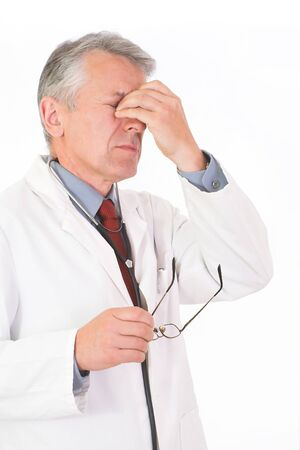 urologist: Vertical image of  matured, graying doctor with stethoscope on his neck  He wears a physician white coat, a blue shirt an a red tie  His face tired  He took off his glasses and makes a massage of  his eyes