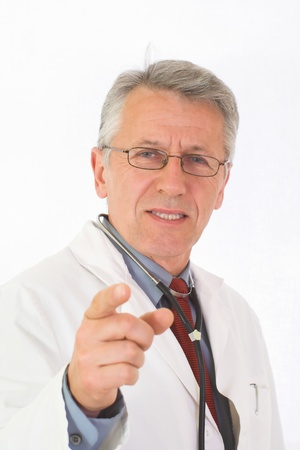 urologist: Vertical portrait of  matured, graying doctor with stethoscope on his neck  His eyes attendive but cheerful  He wears a physician white coat, a blue shirt an a red tie  His forefinger indicates the viewer