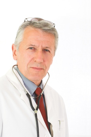 urologist: Vertical portrait of  matured, graying doctor with stethoscope on his neck  His eyes attendive but cheerful  He wears a physician white coat, a blue shirt an a red tie