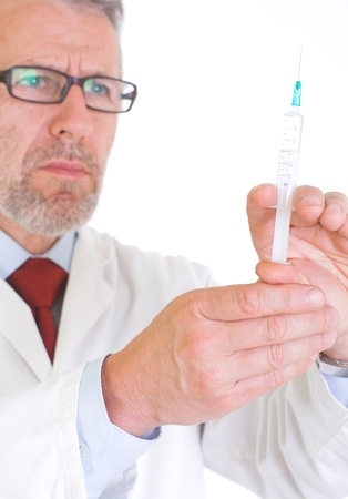 urologist: Image presents a doctor in white coat, getting ready for vaccination – he holds a syringe full of vaccine  Background white   Stock Photo