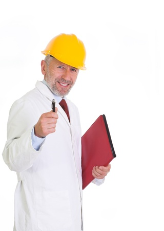 smock: Vertical image presents graying white man, wearing yellow helmet, white smock, blue shirt and tie, who stands, laughing, with a folder of papers and pen in his hands. Stock Photo