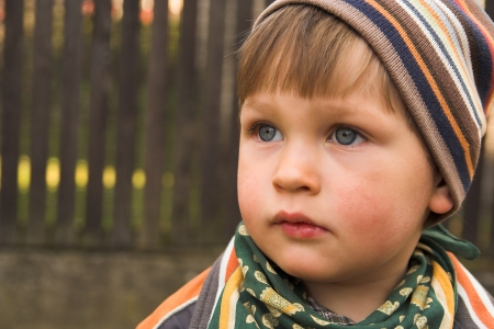 kinder garden: Portrait if the little boy wearing knitted cap, made in the fall in the garden Stock Photo