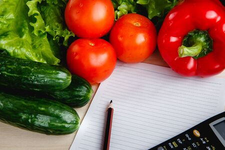 Fresh vegetables on the table: red pepper, lettuce, cucumber, tomatoes, sheet for notes - notepad. Cutting board, Food imitation. Inflation Stock Photo