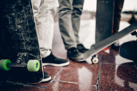 male skateboarder man holds a skate board in his hand against the background of a team of friends. Concept friends are engaged in collective sport