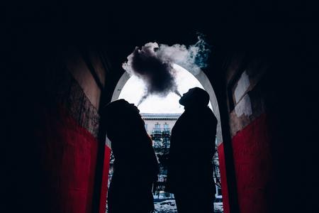 두 연인 남자와 여자 아치에서 vape에서 여자를 내뿜는 커플. 안전한 흡연의 개념, 담배를 포기하십시오.