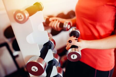Sports equipment dumbbell rests in a row, girl takes a dumbbell in the gym. hands close-up Stock Photo