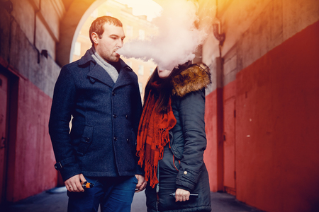 impersonal: couple of men and a girl use electronic cigarettes vape mod and drip. There are clubs of steam. Concept smoking in public places.