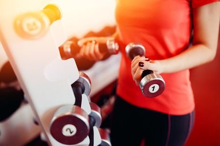 Sports equipment dumbbell rests in a row, girl takes a dumbbell in the gym. hands close-up. hign contrast and monochrome color tone Stock Photo