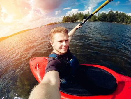 young man requires a kayak on the lake. Shot on the action camera. Stock Photo