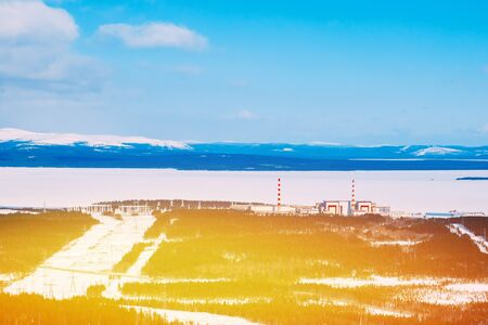 npp: Kola NPP  nuclear power station from the mountain. Industrial landscape. In the background are the mountains of Khibiny and Imandra lake.