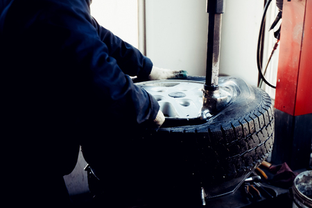 hand brake: car repairman repairs the rubber tire from the car wheel on the balance machine apparatus in the workshop.