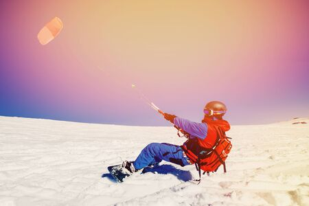 snowkiting: Snowboarder with a kite on fresh snow in the winter in the tundra of Russia against a clear blue sky. Teriberka, Kola Peninsula, Russia. Concept of winter sports snowkite.