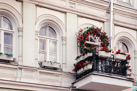 Flowers in pots on the balcony. Concept decoration of the facade.