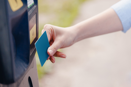 responding: Girl hand inserting ticket into parking machine to pay for parking