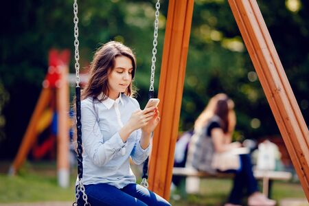 moyens de communication: Girl student teenager swinging on a swing and using the phone for communications. Concept social networks and social activity by means of communication.