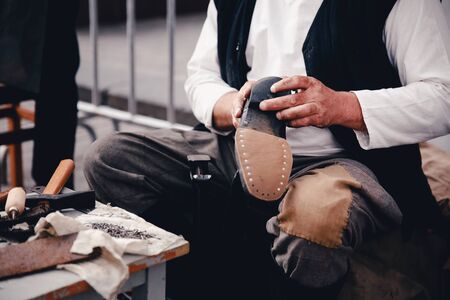 makes: Master tailor makes shoes from leather. Concept of the old customs of making shoes and shoes.