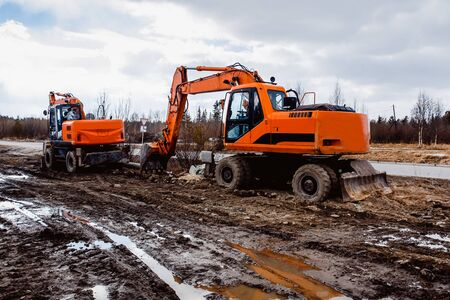 mine site: Two excavators are on the road construction site. Concept of building a house, dig a pit for apartments and houses, Russia. Stock Photo