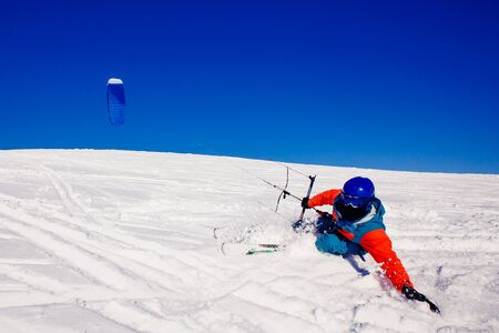 snowkiting: Skier with a kite on fresh snow in the winter in the tundra of Russia against a clear blue sky. Teriberka, Kola Peninsula, Russia. Concept of winter sports snowkite on ski. Stock Photo