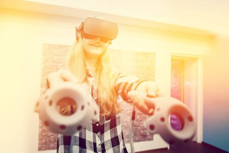 simulator: Blonde girl in glasses and mask for VR. Smiling and laughing. With sunlight and toning. concept of virtual reality.high contrast Stock Photo