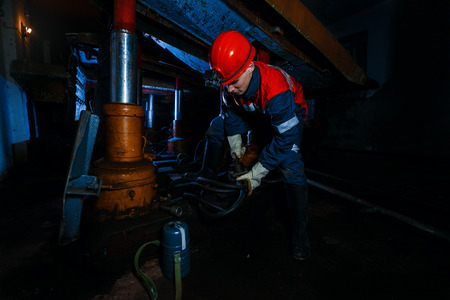 jonge mijnwerker man ondergronds in een mijn voor mijnbouw in overalls is druk met werk, repareren tegen de achtergrond van mijnbouw-apparatuur. Portret. Stockfoto