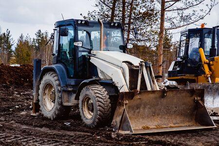 cargador frontal: tractor cargado está estacionado en el barro. Concepto de construcción de carreteras.