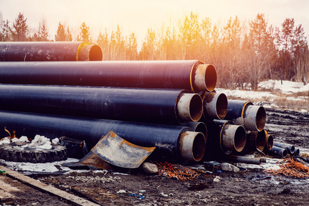 pile stack of big pipes on construction site. Concept of building a house and road, communications. Stock Photo