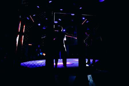 TOMSK, RUSSLAND - 12. Februar 2017: GRAND PRIX Power Club auf MMA. Boxer Kämpfer kommen in Kämpfe ohne Regeln in den Ring-Oktogon. Dunkler hintergrund Hoher Kontrast und monochromer Farbton.