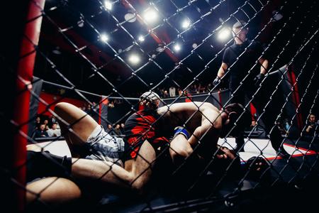 TOMSK, RUSLAND - Februari 12, 2017: GRAND PRIX-Machtsclub op MMA. Boxers fighters komen uit en vechten in gevechten zonder regels in de achthoek. Donkere achtergrond. Hoog contrast en monochrome kleurtint. Redactioneel