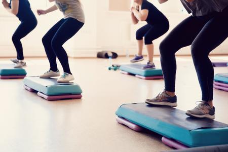 Gruppe von Mädchen ist mit einem Schritt auf dem Stand beschäftigt - Fitness. Das Konzept der Aufrechterhaltung der Gesundheit, zu Fuß. Standard-Bild