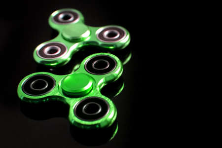 Fidget finger metal spinner, anxiety relief toy on black background, copyspace. Concept relieving stress Stock Photo