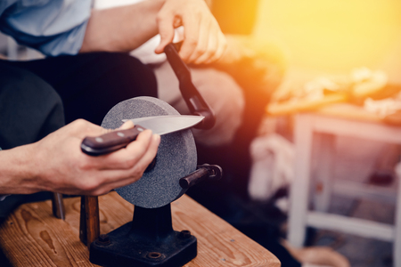 sharpening process: master sharpens the knife by tradition on a hand grindstone. Concept is an old craft, with your own hands. Stock Photo