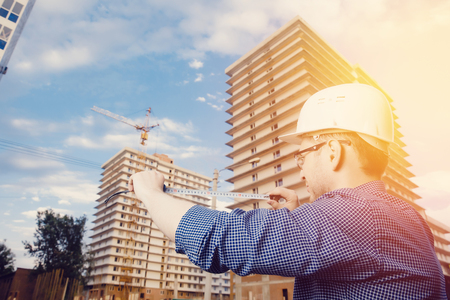 Male construction builder worker - foreman is an engineer in a protective helmet, glasses on the background of building a house with a crane Ruler measures. Concept calculation of construction time and cost. Stock Photo