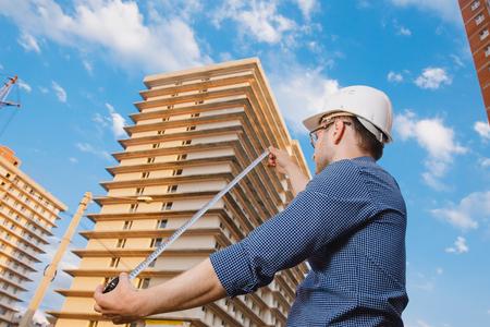Männlich Bau Bauarbeiter Arbeiter - Vorarbeiter ist ein Ingenieur in einem Schutzhelm, Gläser auf dem Hintergrund der Bau eines Hauses mit einem Kran Herrscher Maßnahmen. Konzept Berechnung der Bauzeit und Kosten.