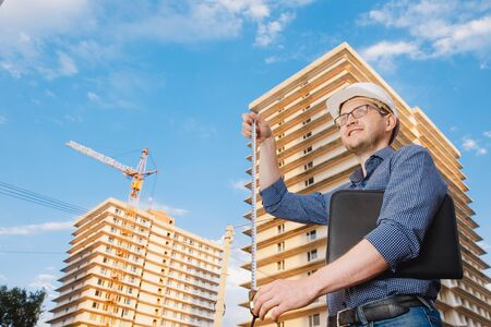 Male construction builder worker - foreman is engineer in protective helmet, glasses on background building a house with crane Ruler measures.